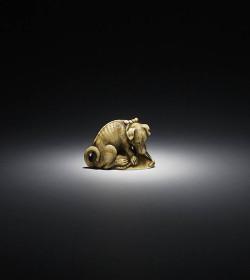 Ivory netsuke of a dog with awabi shell
