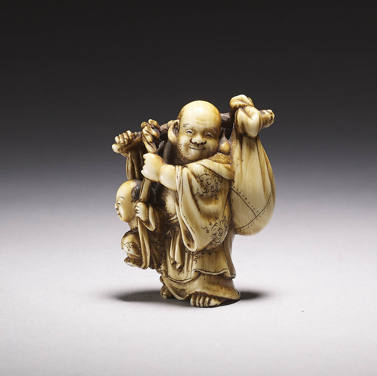 Chikuyōsai Tomochika dark stained ivory netsuke of Hotei with karako
