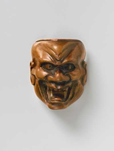 Pale boxwood mask netsuke of Shikami,