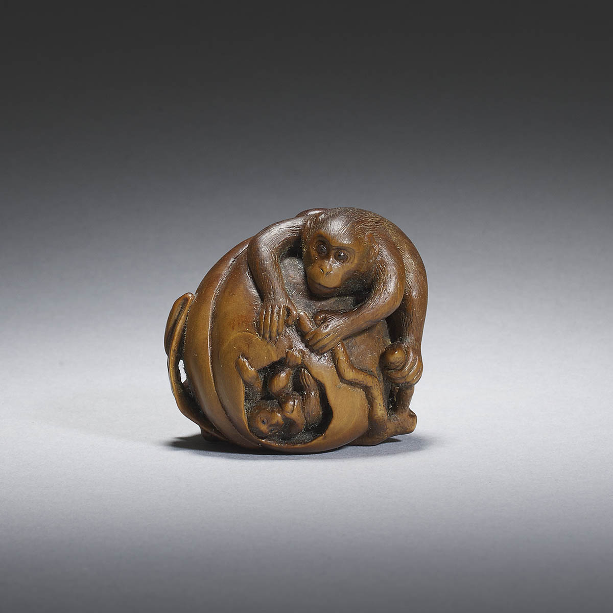 Boxwood netsuke of monkeys on a giant peach