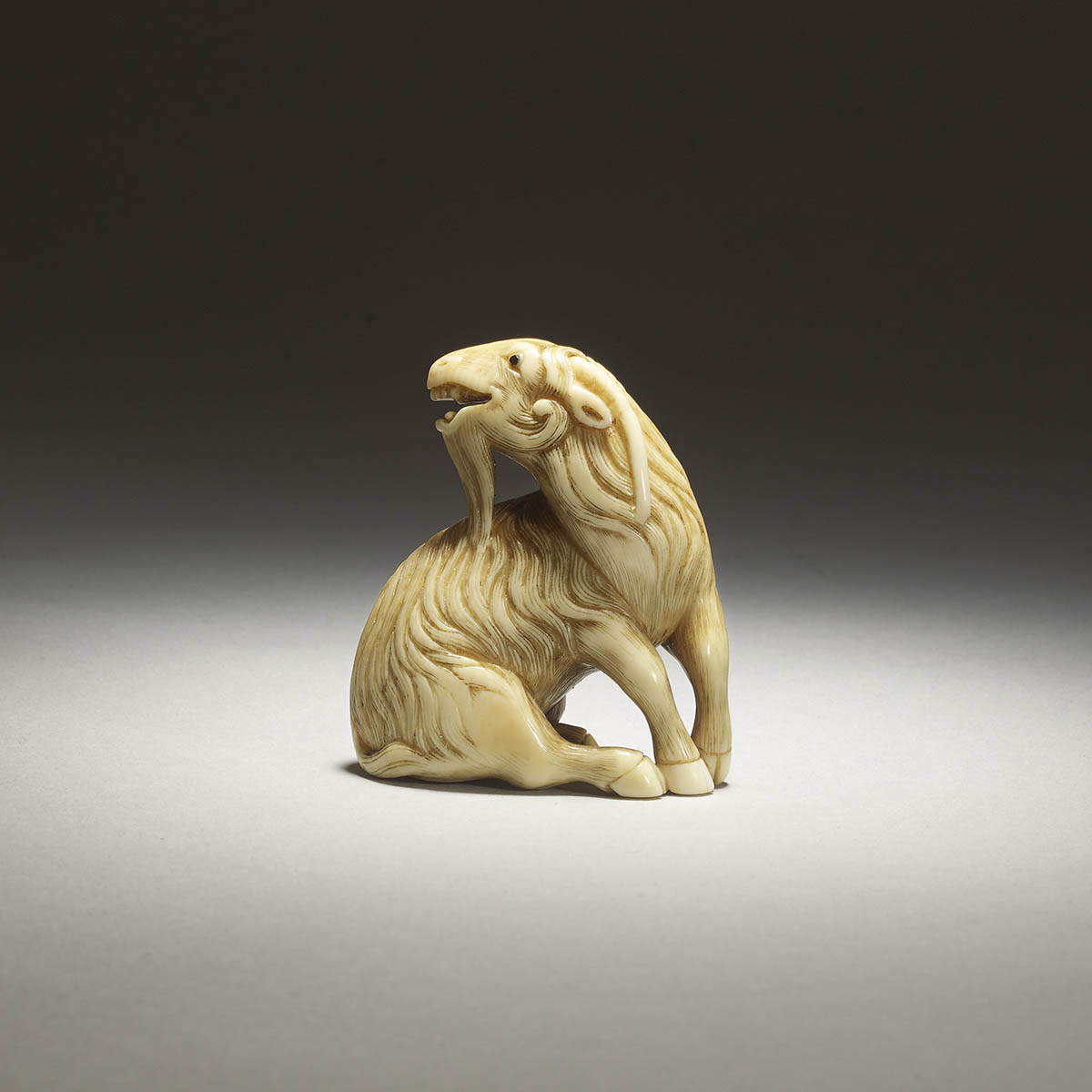 Mitsuharu, ivory netsuke of a seated goat