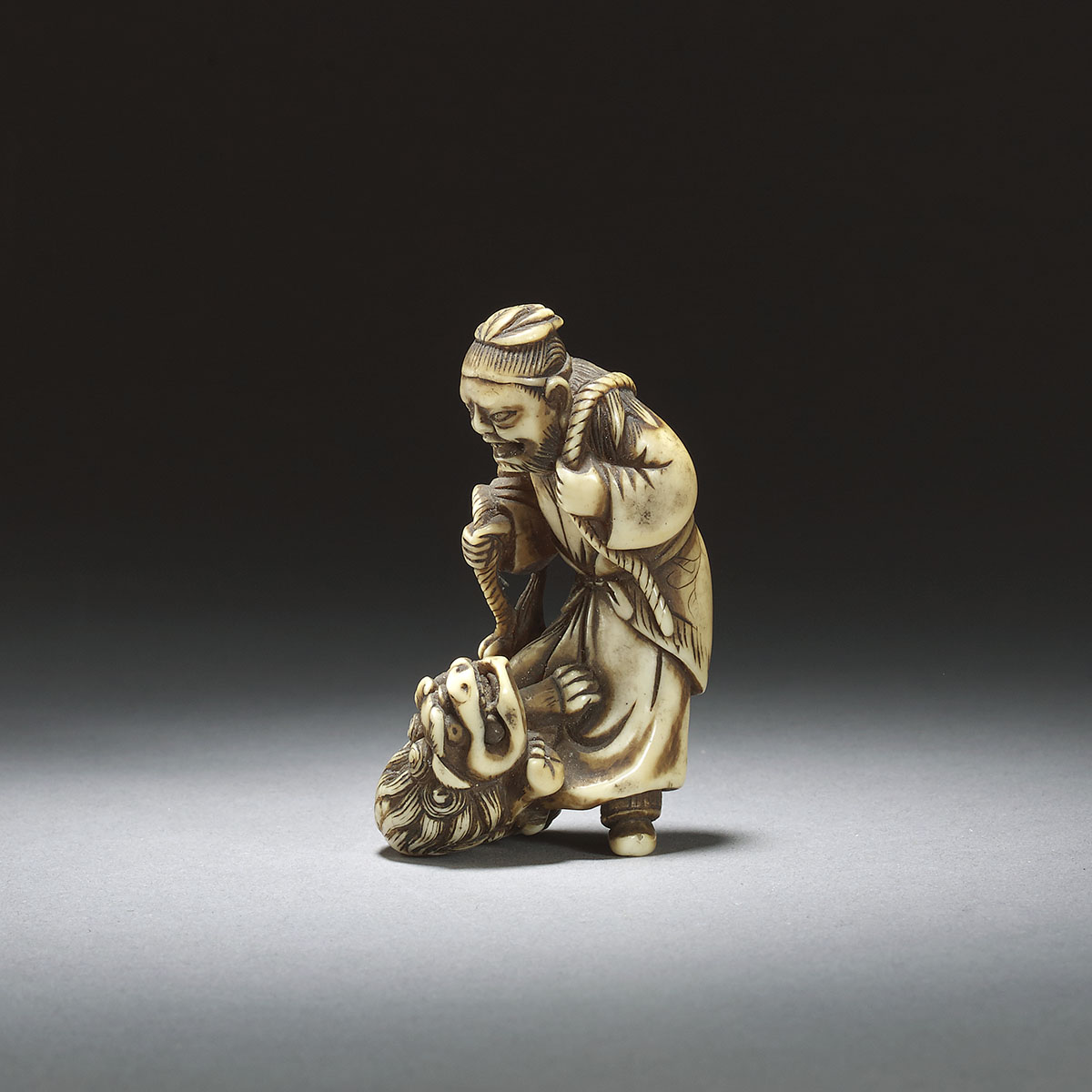 Netsuke of a man with shishi