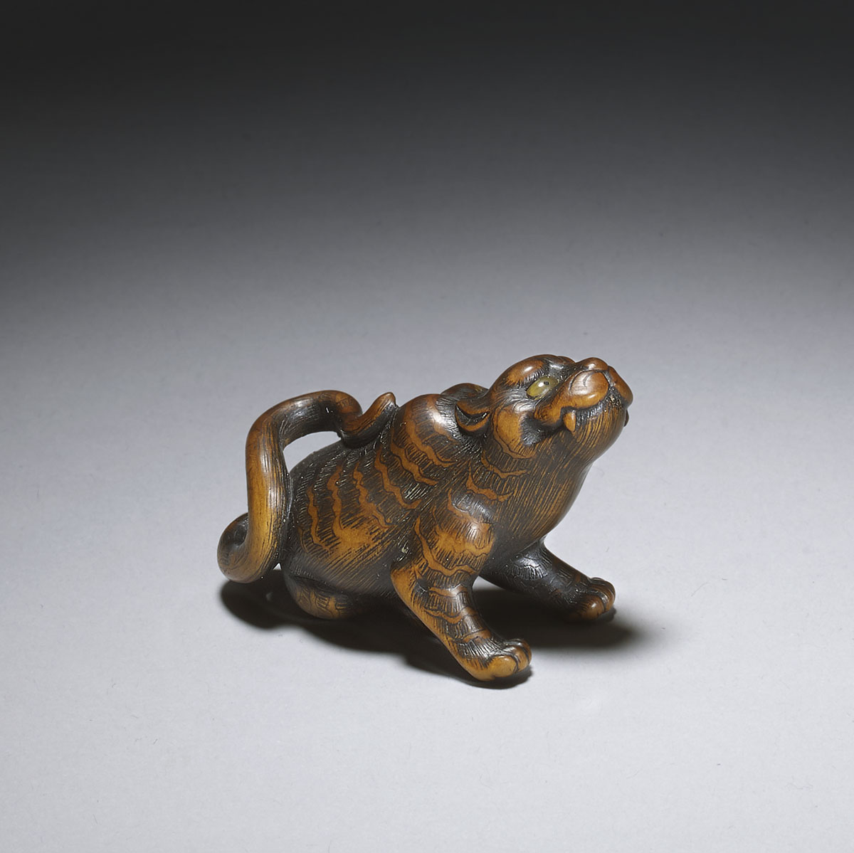 Toyomasa, wood netsuke of a seated scratching tiger