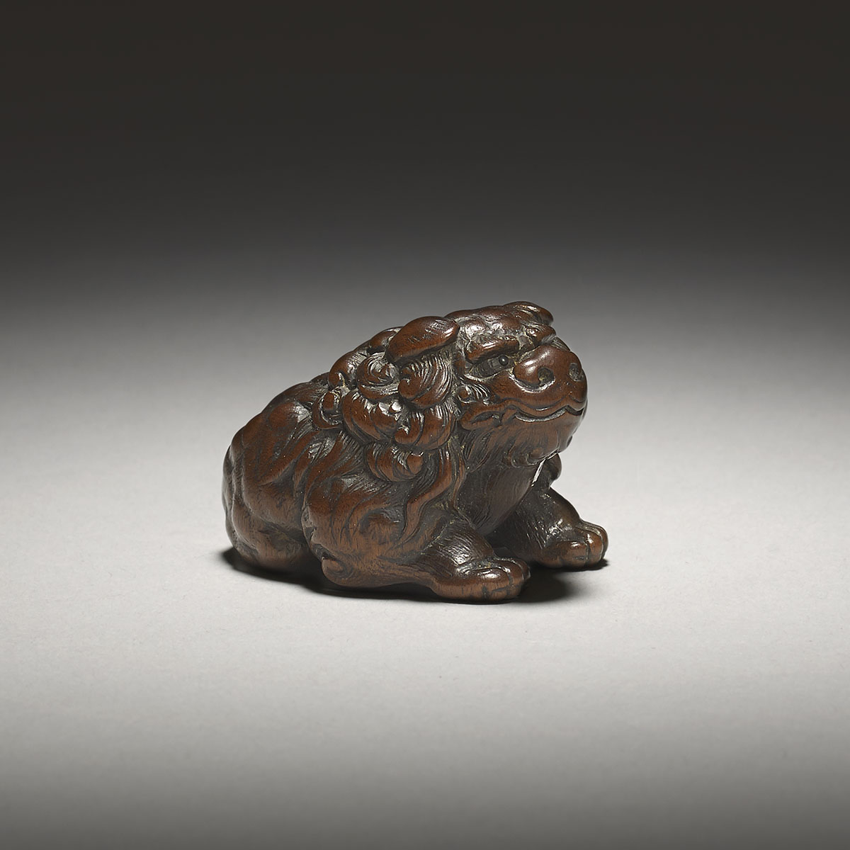 Dark stained boxwood netsuke of a seated shishi, Tōmin,MR3118_v2
