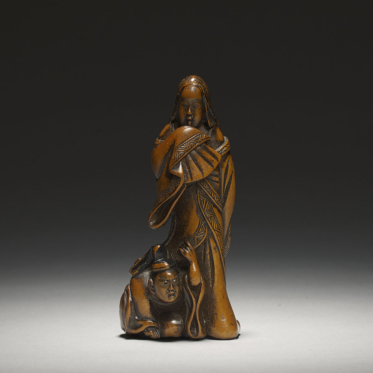 Wood netsuke of a Heian lady with courtier hiding under her robe, MR3097_v1