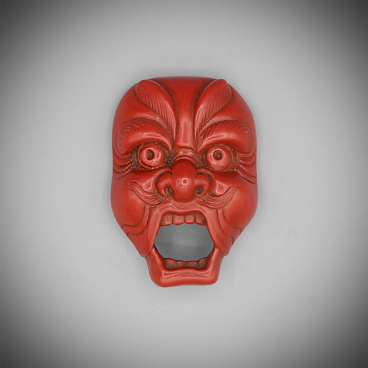 Carved red lacquer mask netsuke of Genjoraku, Hosai, MR3143_v1