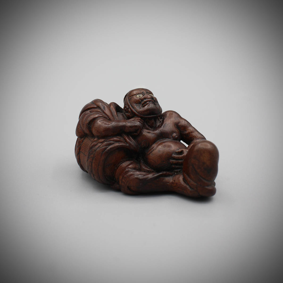 Plum wood netsuke of a man leaning against a saké barrel, Miwa, MR3164_v1