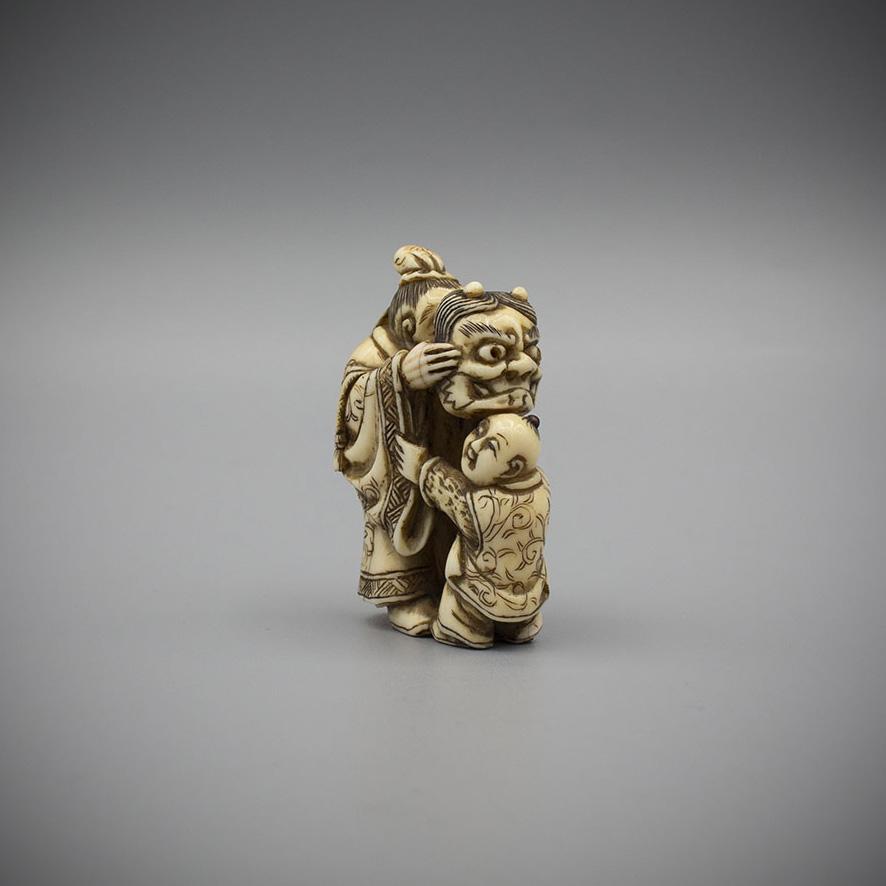 Ivory netsuke of a man teasing a karako with an oni mask by Hidemasa, MR2844_v1-2