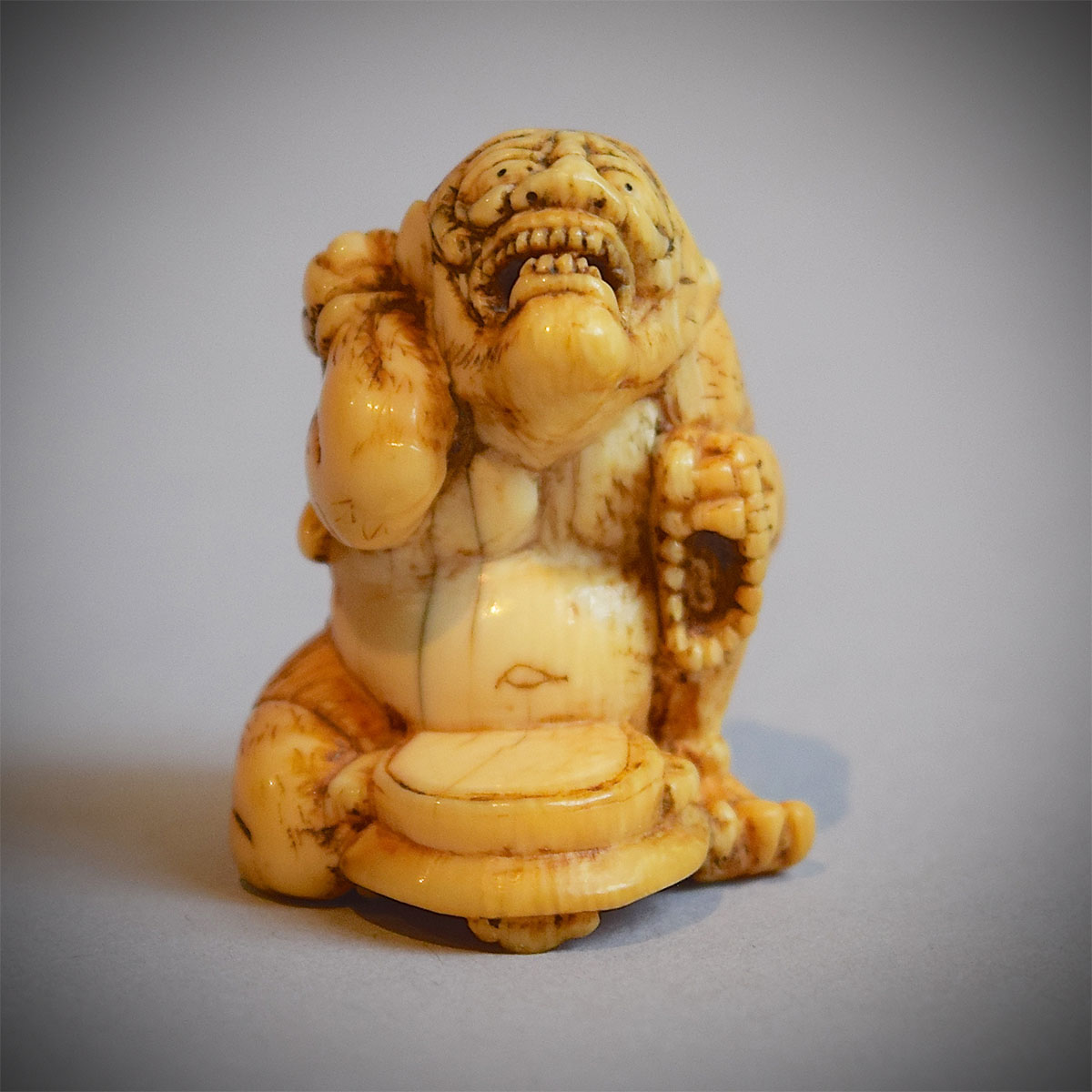 Ivory netsuke of an oni beating a drum, MR976_v1