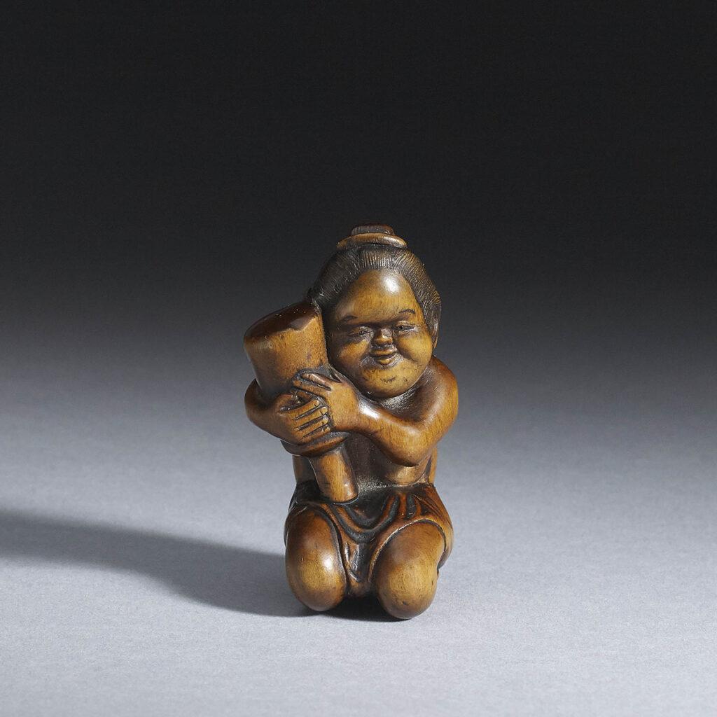 Netsuke of a Recumbent Shishi | Max Rutherston Ltd