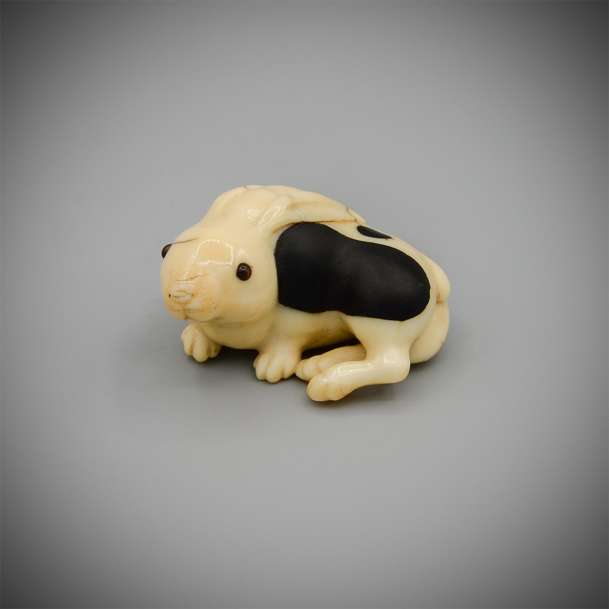 An inlaid narwhal ivory netsuke of a hare or rabbit by Oshomitsu, MR3651