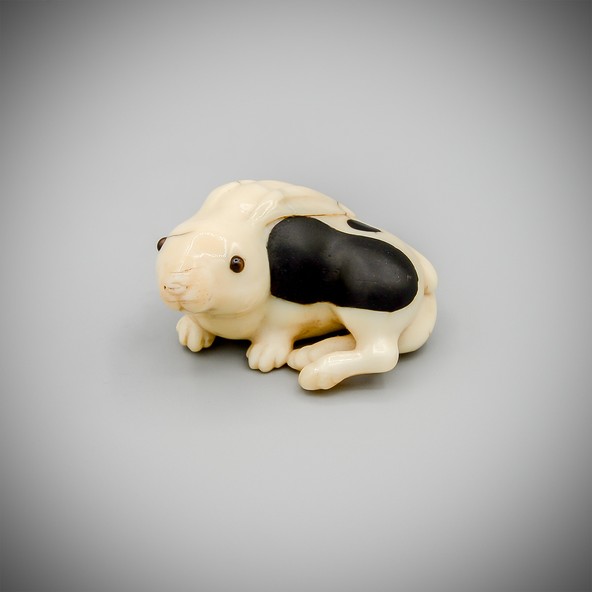 An inlaid narwhal ivory netsuke of a hare or rabbit by Oshomitsu, MR3651_v.1-2