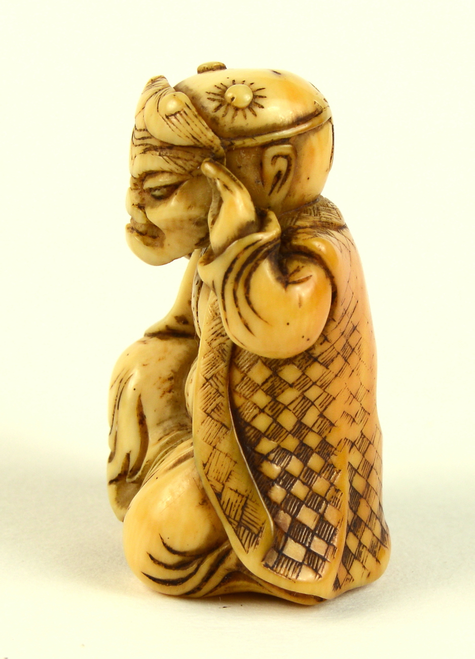 Ivory netsuke of boy with oni mask left profile