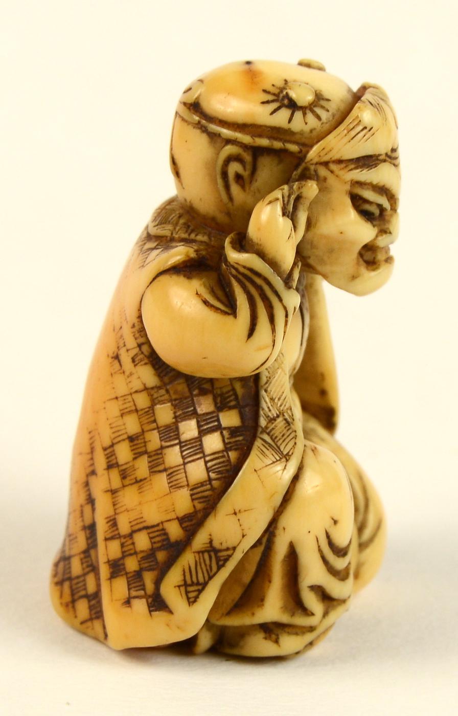 Ivory netsuke of boy with oni mask right profile