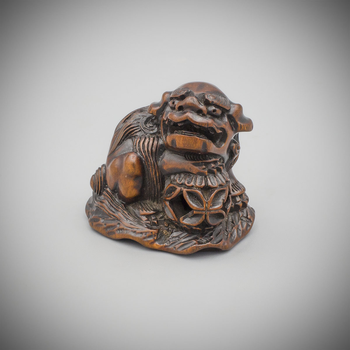 MR3691_v.1 Dark stained wood netsuke of a shishi by Minkoku
