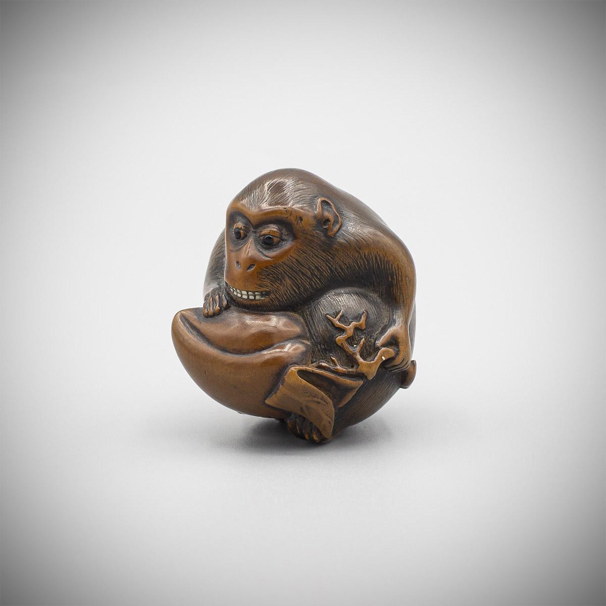 Rare wood netsuke of a monkey with peach by Naito Toyomasa